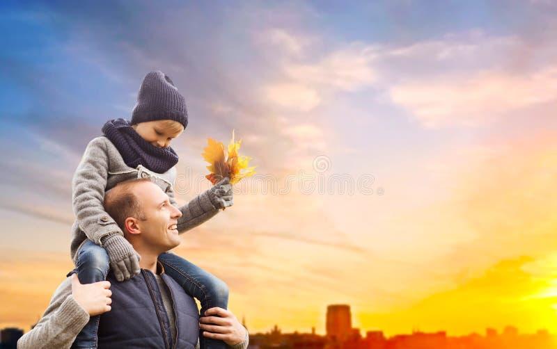 Φέρνοντας γιος πατέρων με τα φύλλα φθινοπώρου στην πόλη στοκ φωτογραφία με δικαίωμα ελεύθερης χρήσης