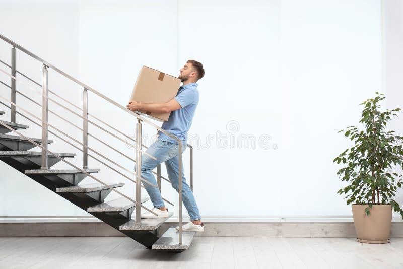 Φέρνοντας κιβώτιο χαρτοκιβωτίων νεαρών άνδρων επάνω στο εσωτερικό στοκ φωτογραφίες