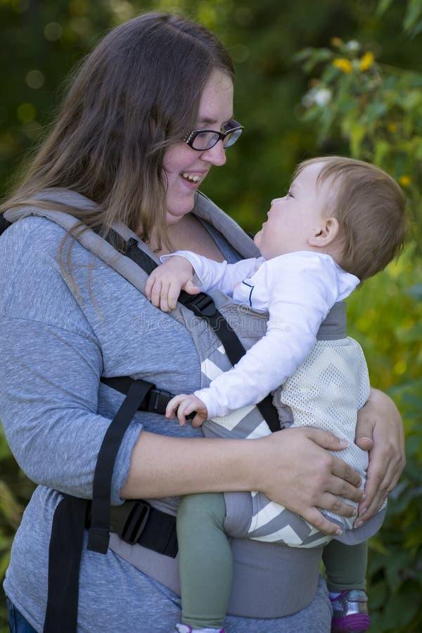 Φέρνοντας κοριτσάκι Mom με το μεταφορέα, που απολαμβάνει την ημέρα στο πάρκο στοκ εικόνες