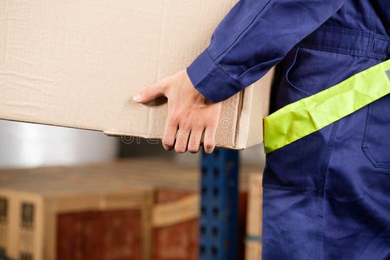 Φέρνοντας κουτί από χαρτόνι επιστατών στην αποθήκη εμπορευμάτων στοκ εικόνες