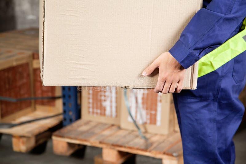Φέρνοντας κουτί από χαρτόνι επιστατών στην αποθήκη εμπορευμάτων στοκ φωτογραφίες