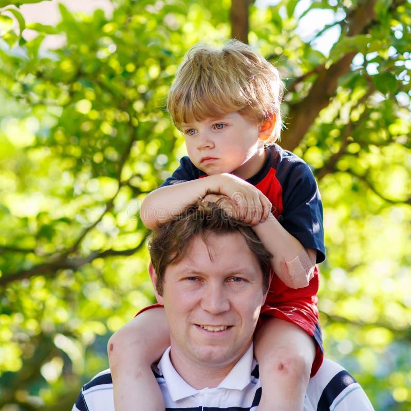 Φέρνοντας παιδί πατέρων στους ώμους του στο πάρκο στοκ εικόνες