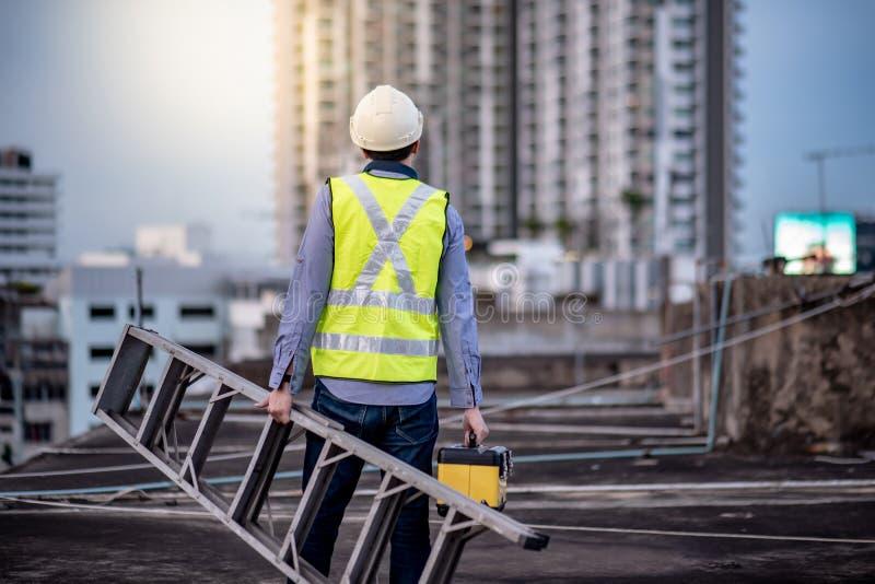Φέρνοντας σκάλα αλουμινίου ατόμων εργαζομένων και κιβώτιο εργαλείων στοκ φωτογραφία