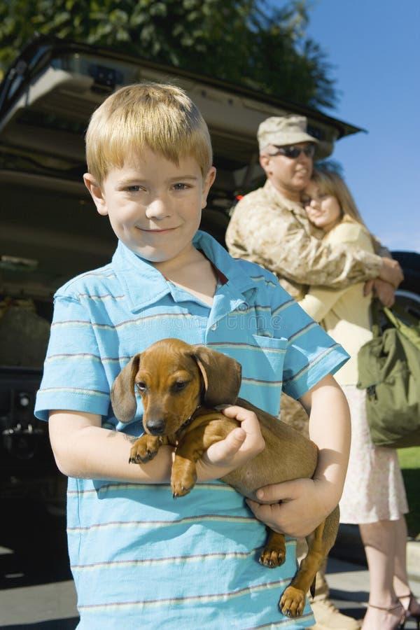 Φέρνοντας σκυλί αγοριών με τους γονείς στο υπόβαθρο στοκ εικόνα