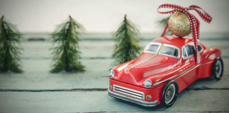 Φέρνοντας σφαίρα μπιχλιμπιδιών Χριστουγέννων αυτοκινήτων παιχνιδιών στην ξύλινη σανίδα στοκ φωτογραφία