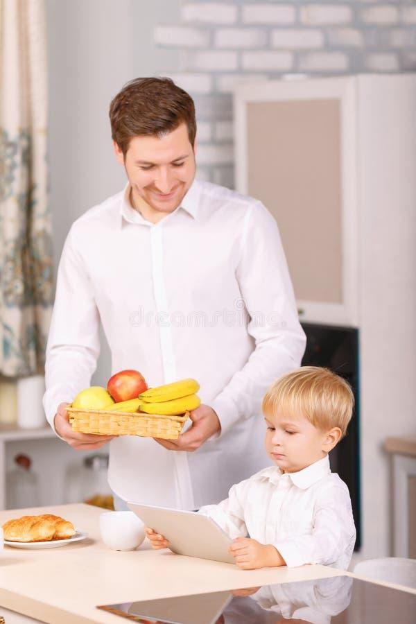 Φέρνοντας φρούτα και γιος πατέρων με την ψηφιακή ταμπλέτα στοκ εικόνα