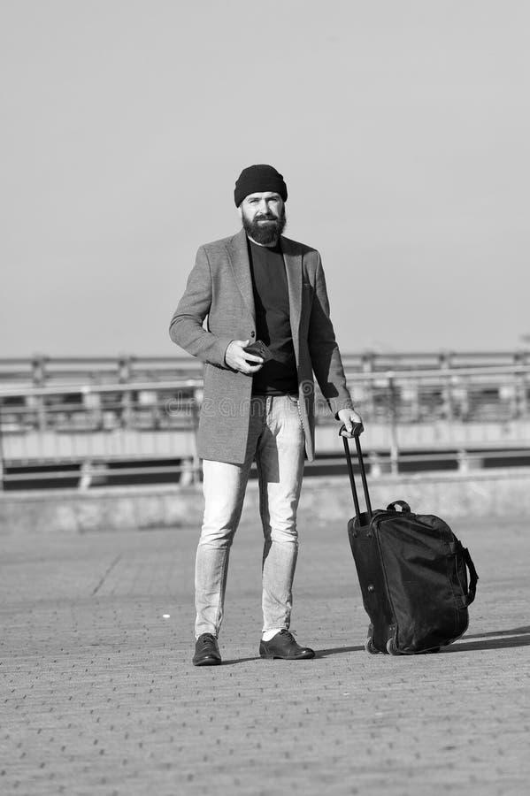 Φέρτε την τσάντα ταξιδιού Επαγγελματικό ταξίδι Γενειοφόρο ταξίδι hipster ατόμων με τη μεγάλη τσάντα αποσκευών στις ρόδες Αφήστε τ στοκ εικόνες