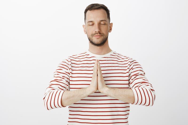 Φέρτε τις κακές σκέψεις μακριά με τη γιόγκα Το πορτρέτο του ήρεμου χαλαρωμένου ελκυστικού τύπου στο ριγωτό πουλόβερ, κράτημα παρα στοκ φωτογραφία