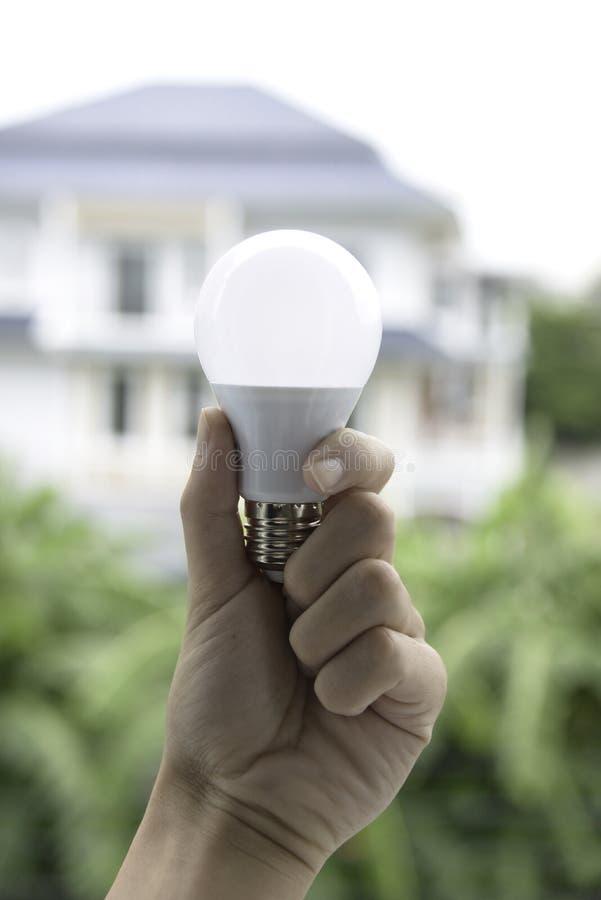 Φέρτε lightbulb σε διαθεσιμότητα με το υπόβαθρο σπιτιών στοκ φωτογραφία με δικαίωμα ελεύθερης χρήσης