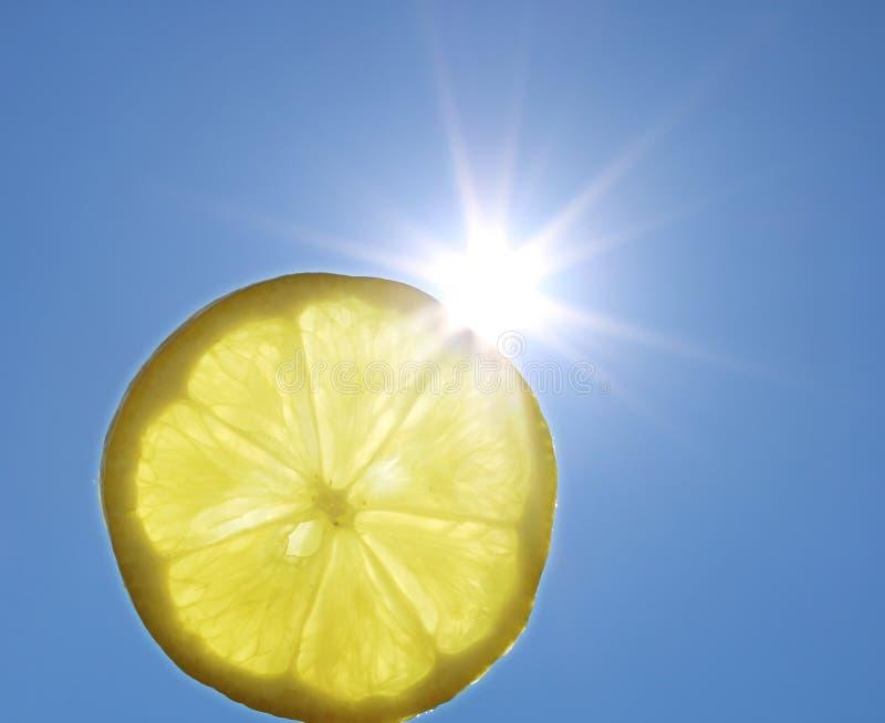 Φέτα λεμονιών καλοκαιρινών διακοπών μπροστά από τον ήλιο και το μπλε ουρανό στοκ εικόνα με δικαίωμα ελεύθερης χρήσης
