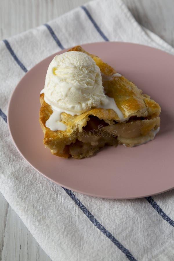 Φέτα της σπιτικής πίτας μήλων με το παγωτό βανίλιας σε ένα ρόδινο πιάτο, πλάγια όψη E στοκ εικόνα