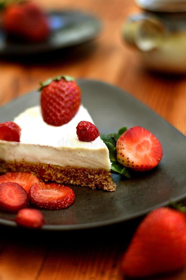 Φέτα του ακατέργαστου κέικ φραουλών σε ένα καφετί πιάτο στοκ φωτογραφίες με δικαίωμα ελεύθερης χρήσης