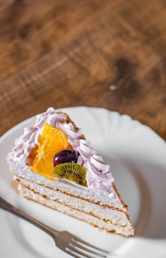 Φέτα του βαλμένου σε στρώσεις κέικ γενεθλίων με την κρέμα με τα φρούτα σε ένα πιάτο σε ξύλινο στοκ φωτογραφίες