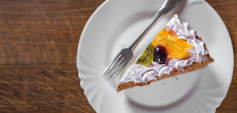 Φέτα του βαλμένου σε στρώσεις κέικ γενεθλίων με την κρέμα με τα φρούτα σε ένα πιάτο σε ξύλινο στοκ φωτογραφίες με δικαίωμα ελεύθερης χρήσης