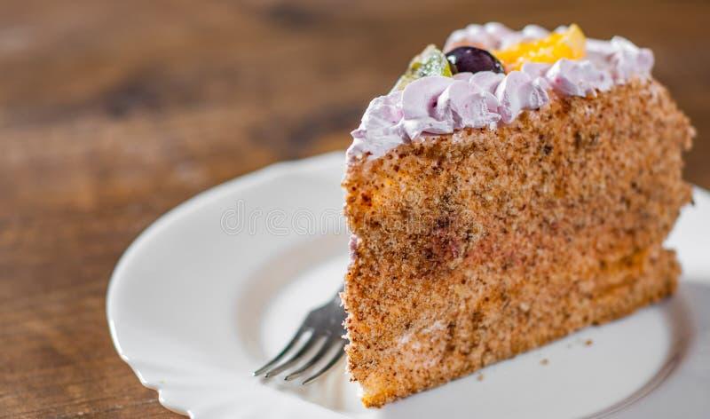 Φέτα του βαλμένου σε στρώσεις κέικ γενεθλίων με την κρέμα με τα φρούτα σε ένα πιάτο σε ξύλινο στοκ φωτογραφία με δικαίωμα ελεύθερης χρήσης
