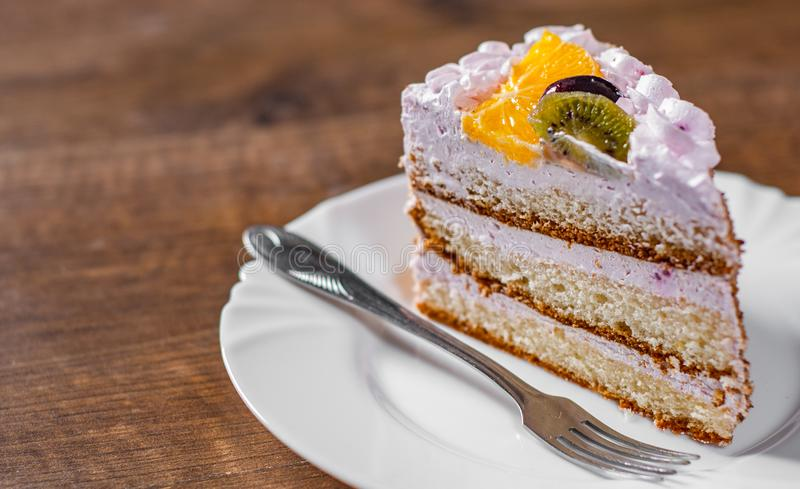 Φέτα του βαλμένου σε στρώσεις κέικ γενεθλίων με την κρέμα με τα φρούτα σε ένα πιάτο σε ξύλινο στοκ εικόνα με δικαίωμα ελεύθερης χρήσης