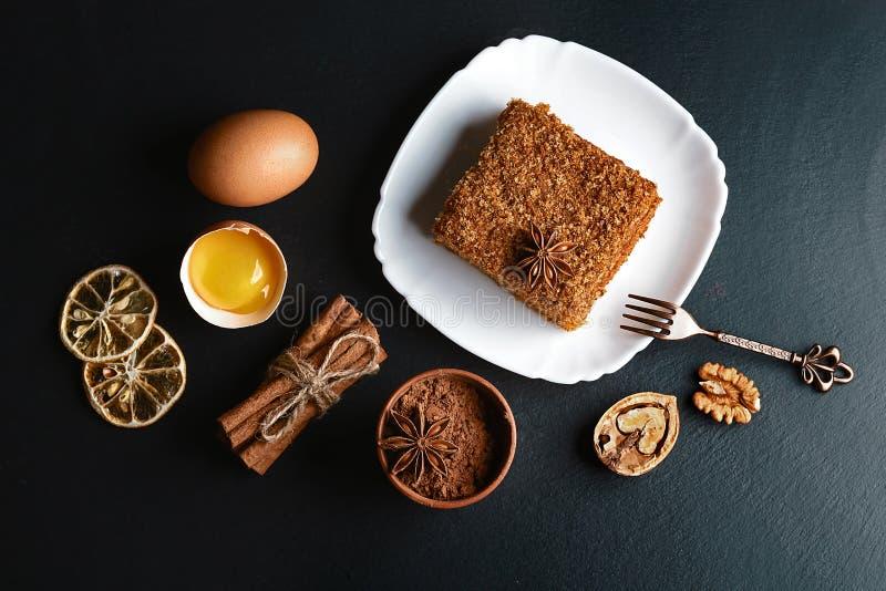 Φέτα του βαλμένου σε στρώσεις κέικ μελιού που διακοσμείται με το αστέρι γλυκάνισου, δίκρανο επιδορπίων, ξηρά λεμόνια, ραβδιά της  στοκ εικόνες με δικαίωμα ελεύθερης χρήσης