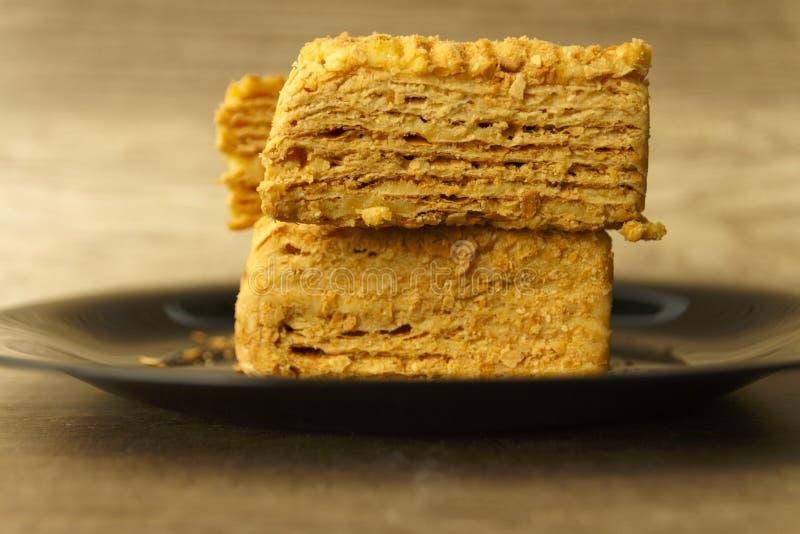 Φέτα του πορτοκαλιού κέικ στο μαύρο πιάτο στον ξύλινο πίνακα, υπόβαθρο τροφίμων στοκ φωτογραφία με δικαίωμα ελεύθερης χρήσης