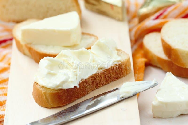 Φέτα του ψωμιού με το τυρί κρέμας και του βουτύρου για το πρόγευμα στοκ φωτογραφίες