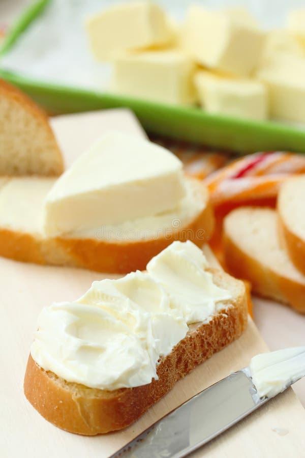 Φέτα του ψωμιού με το τυρί κρέμας και του βουτύρου για το πρόγευμα στοκ εικόνα