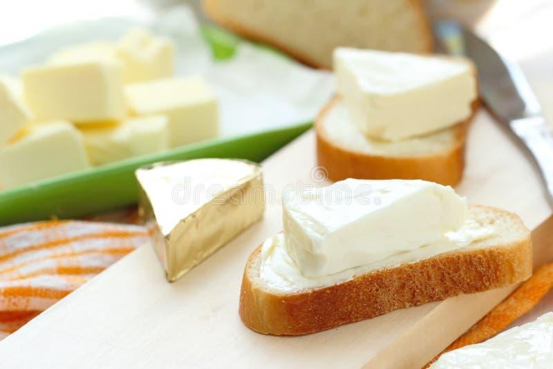 Φέτα του ψωμιού με το τυρί κρέμας και του βουτύρου για το πρόγευμα στοκ εικόνες