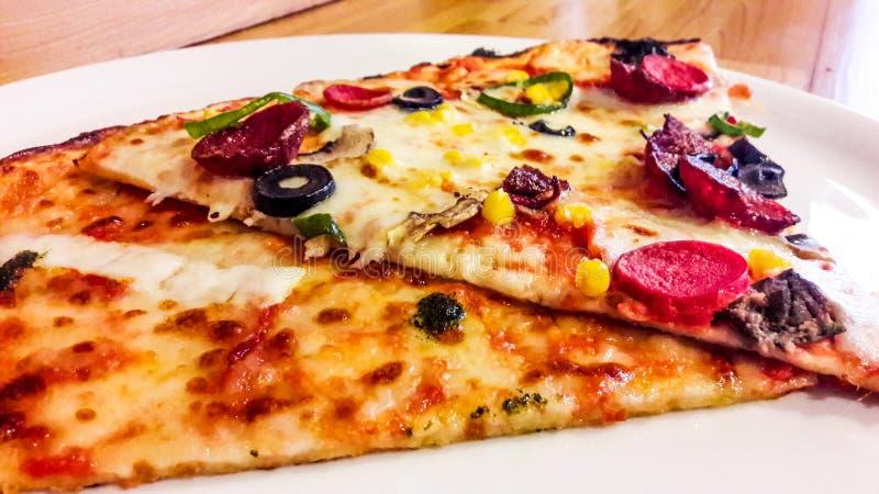 Φέτα δύο της Μαργαρίτα και της πίτσας λουκάνικων στο άσπρο πιάτο στοκ εικόνα