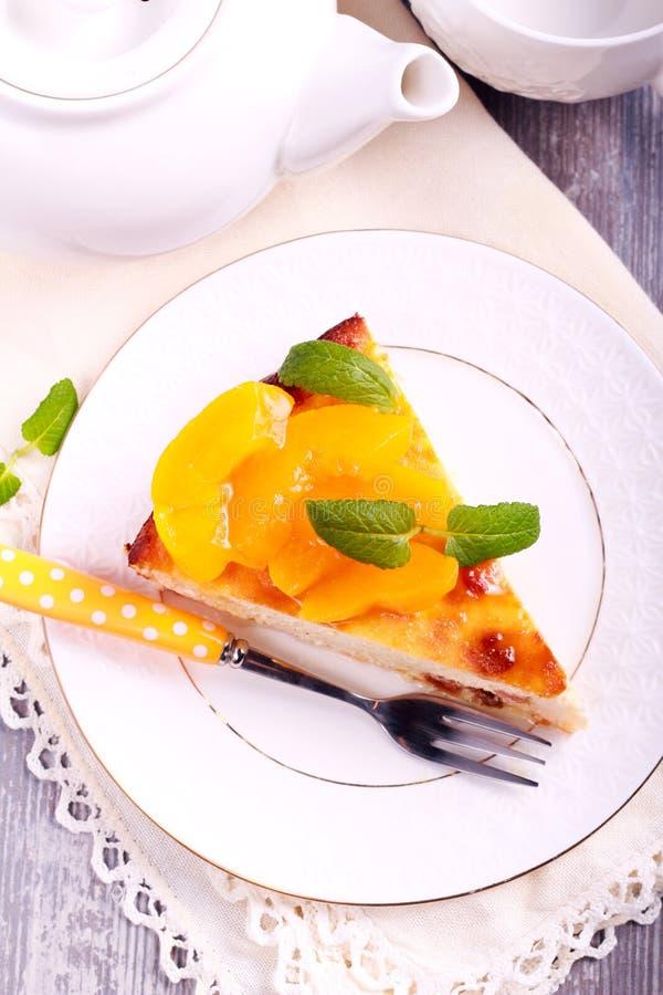 Φέτα cheesecake με το ροδάκινο στην κορυφή, στο πιάτο στοκ φωτογραφία
