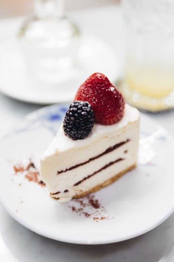 Φέτα cheesecake φραουλών του καλύμματος με τη φρέσκα φράουλα και το βατόμουρο Εξυπηρετημένος με τη σόδα mocktail και το σιρόπι στοκ εικόνα με δικαίωμα ελεύθερης χρήσης