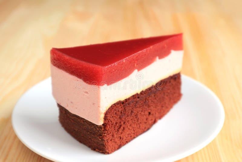 Φέτα Mousse σμέουρων με το κέικ στρώματος σοκολάτας που εξυπηρετείται στον ξύλινο πίνακα στοκ εικόνα με δικαίωμα ελεύθερης χρήσης