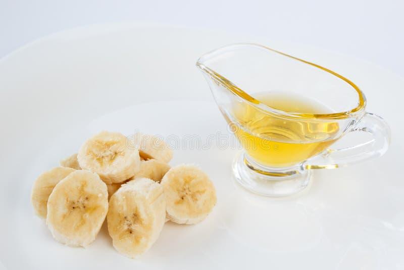 Φέτες και μέλι μπανανών σε μια βάρκα ζωμού γυαλιού στοκ φωτογραφίες με δικαίωμα ελεύθερης χρήσης