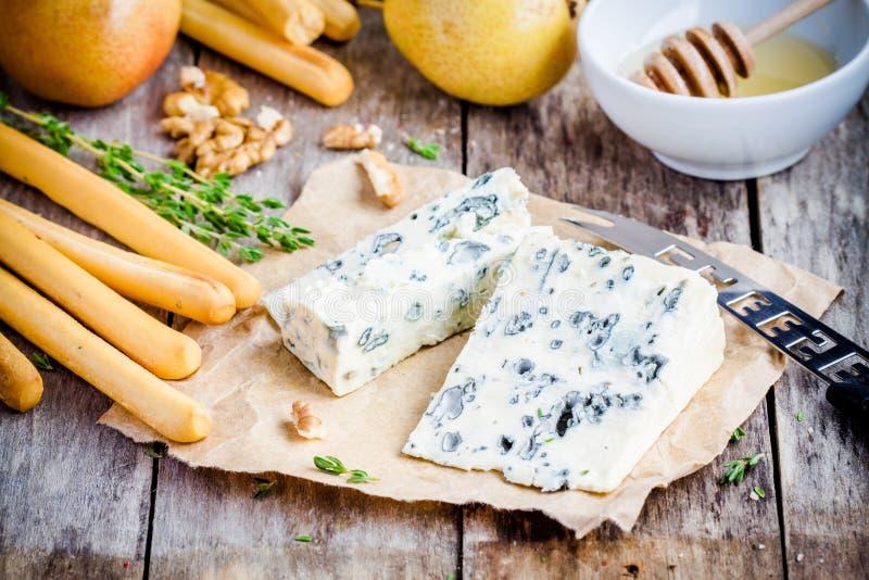 Φέτες μπλε τυριών με τα breadsticks, τα καρύδια και το μέλι στοκ εικόνες