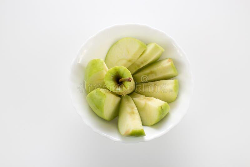 Φέτες της Apple στο μικρό άσπρο κύπελλο στοκ εικόνες
