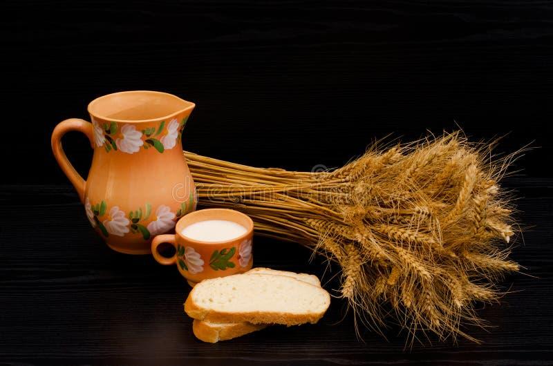 Φέτες του άσπρου ψωμιού, ενός φλυτζανιού του γάλακτος και μιας κανάτας, sheaf των αυτιών σίτου σε έναν μαύρο πίνακα στοκ εικόνα