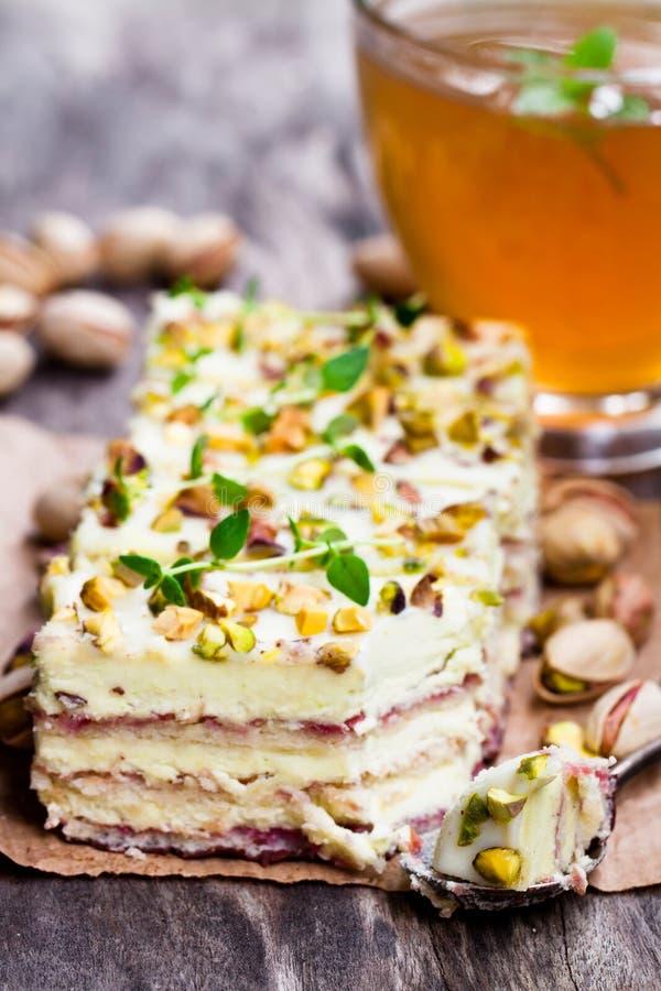 Φέτες του βαλμένου σε στρώσεις κέικ με το φυστίκι και ενός φλυτζανιού πράσινου βοτανικού στοκ φωτογραφία με δικαίωμα ελεύθερης χρήσης