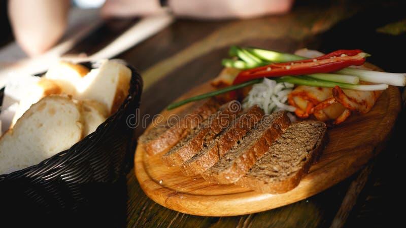 Φέτες του καπνισμένου στήθους, παχύ μπέϊκον, ξηρό πιπέρι τσίλι, κομμάτια του ψωμιού στοκ φωτογραφίες