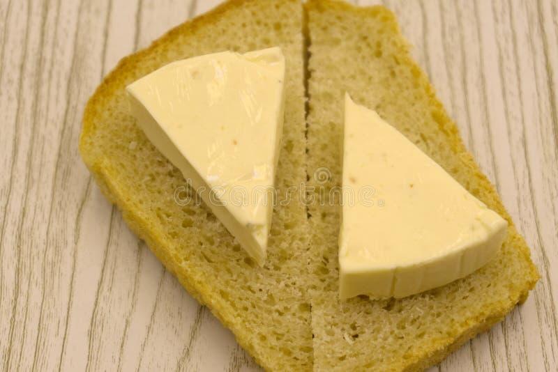 Φέτες του μαύρου ψωμιού με τους σπόρους σουσαμιού και του τυριού στο παλαιό ξύλινο υπόβαθρο στοκ φωτογραφία με δικαίωμα ελεύθερης χρήσης