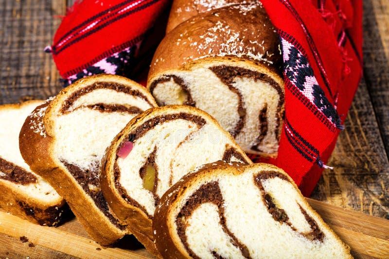 Φέτες του ρουμανικού κέικ σφουγγαριών με την κόκκινη παραδοσιακή πετσέτα στοκ εικόνα