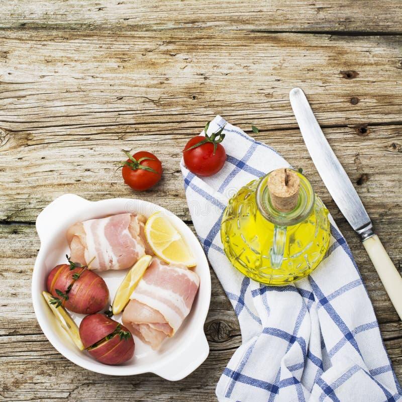 Φέτες του στήθους κοτόπουλου που τυλίγονται στο μπέϊκον με τις πατάτες και τα χορτάρια σε μια κεραμική μορφή πρίν ψήνει στο φούρν στοκ εικόνα με δικαίωμα ελεύθερης χρήσης