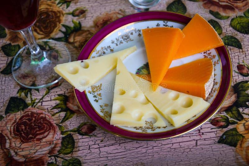 Φέτες του τυριού σε ένα πιάτο με ένα ποτήρι του κρασιού στοκ εικόνες