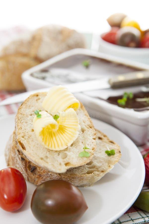 Φέτες του ψωμιού και του βουτύρου με τις ντομάτες, τα πιπέρια και το πατέ στοκ εικόνες
