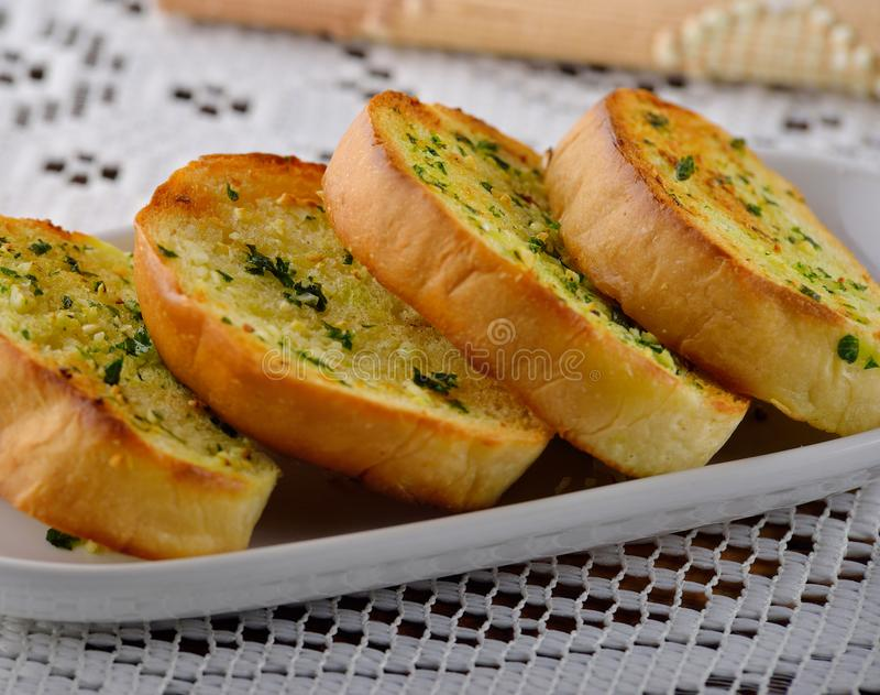 Φέτες ψωμιού σκόρδου και χορταριών στο άσπρο πιάτο στοκ φωτογραφίες με δικαίωμα ελεύθερης χρήσης