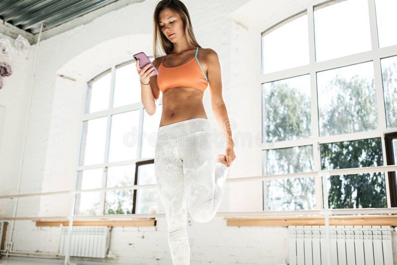 Φίλαθλες γυναικών τεντώματος ποδιών και λαβής ασκήσεις μελετών χεριών smartphone διαθέσιμες σε μια εφαρμογή αθλητικής ικανότητας στοκ φωτογραφία