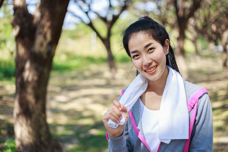 Φίλαθλη γυναίκα με την άσπρη πετσέτα που στηρίζεται μετά από το αθλητικό exerci workout στοκ εικόνα