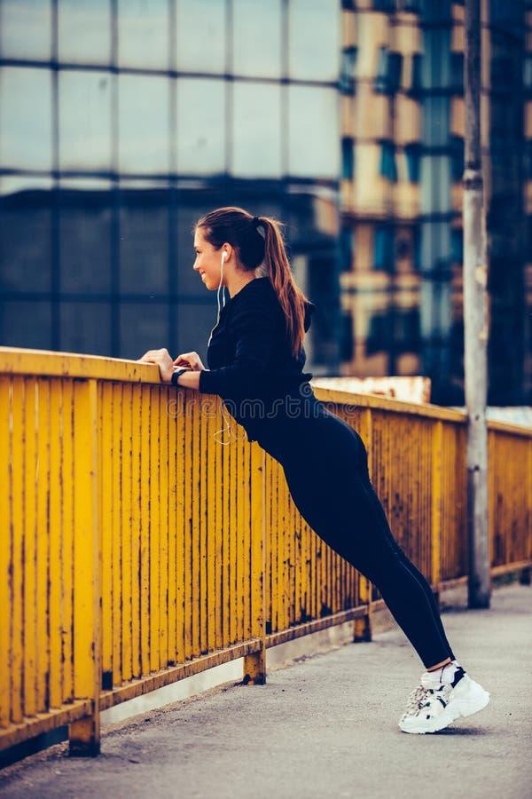 Φίλαθλη γυναίκα που κάνει τις τεντώνοντας ασκήσεις στη γέφυρα και που προετοιμάζεται για την αθλητική κατάρτιση στοκ εικόνα