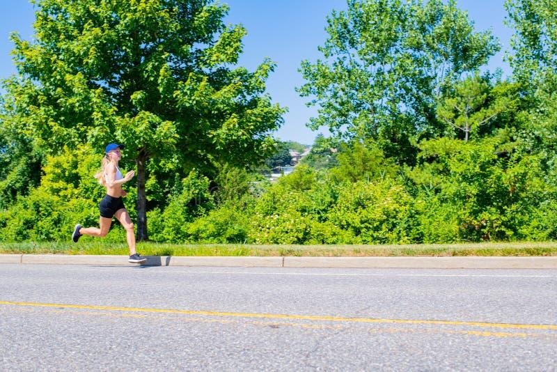 Φίλαθλη γυναίκα sportswear στο ίχνος που τρέχει στο δρόμο Το κορίτσι αθλητών στο πάρκο στοκ φωτογραφίες