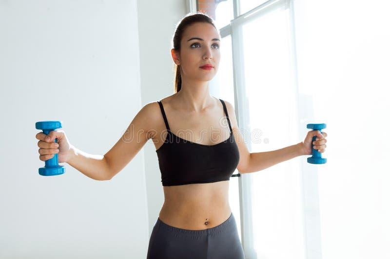 Φίλαθλη νέα γυναίκα που κάνει τη μυϊκή άσκηση με τους αλτήρες εσωτερικούς στοκ φωτογραφία με δικαίωμα ελεύθερης χρήσης