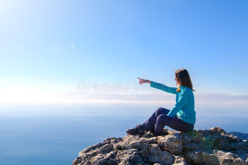 Φίλαθλη νέα συνεδρίαση γυναικών σε μια δύσκολη κορυφή του βουνού ενάντια στο μπλε του ουρανού και της θάλασσας στοκ φωτογραφίες
