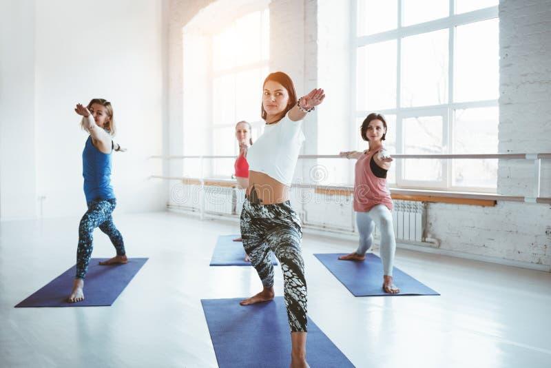 Φίλαθλη ομάδα λεπτής γυναίκας που κάνει την άσκηση γιόγκας στο άσπρο διάστημα γυμναστικής Κατηγορία ικανότητας και υγιής τρόπος ζ στοκ εικόνες