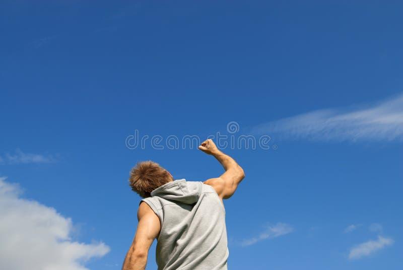 Φίλαθλος νεαρός άνδρας με το βραχίονά του που αυξάνεται στη χαρά στοκ φωτογραφία