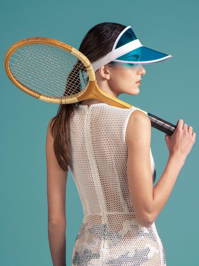 Φίλαθλος τενίστας γυναικών με τη ρακέτα αντισφαίρισης στο μπλε backgroun στοκ φωτογραφίες
